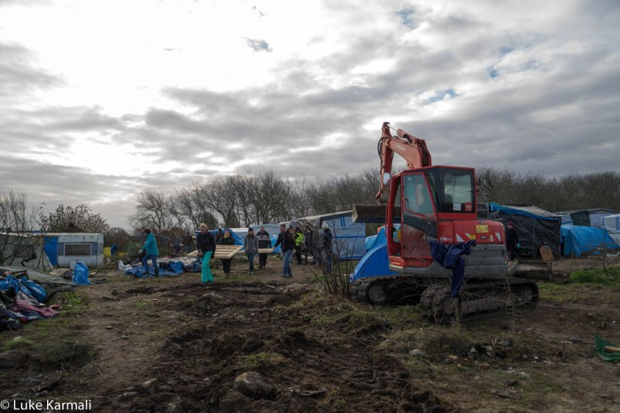 Volunteers help to build new shelter and clear old, broken tents, and those that are simply being cleared to make way for the new structures. This is a divisive issue.