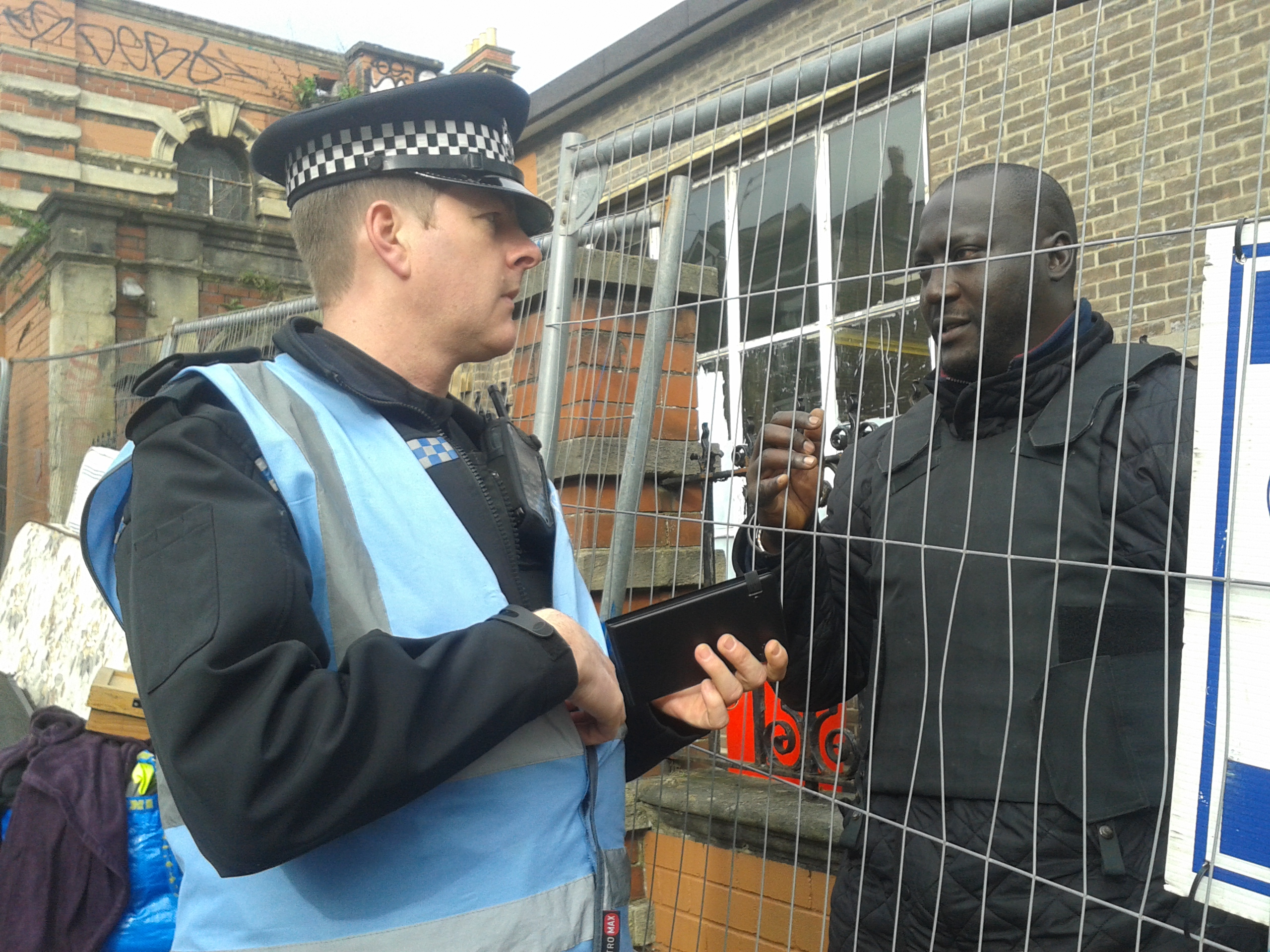 Police man talking to a person of colour though a fence