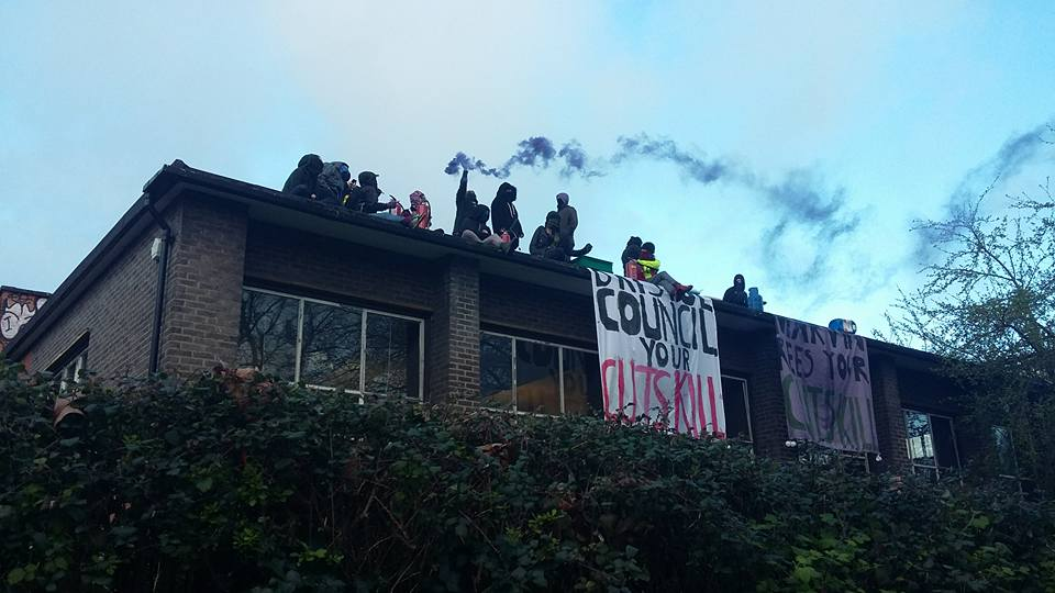 People on a roof with a banner reading: bristol council your cuts kill