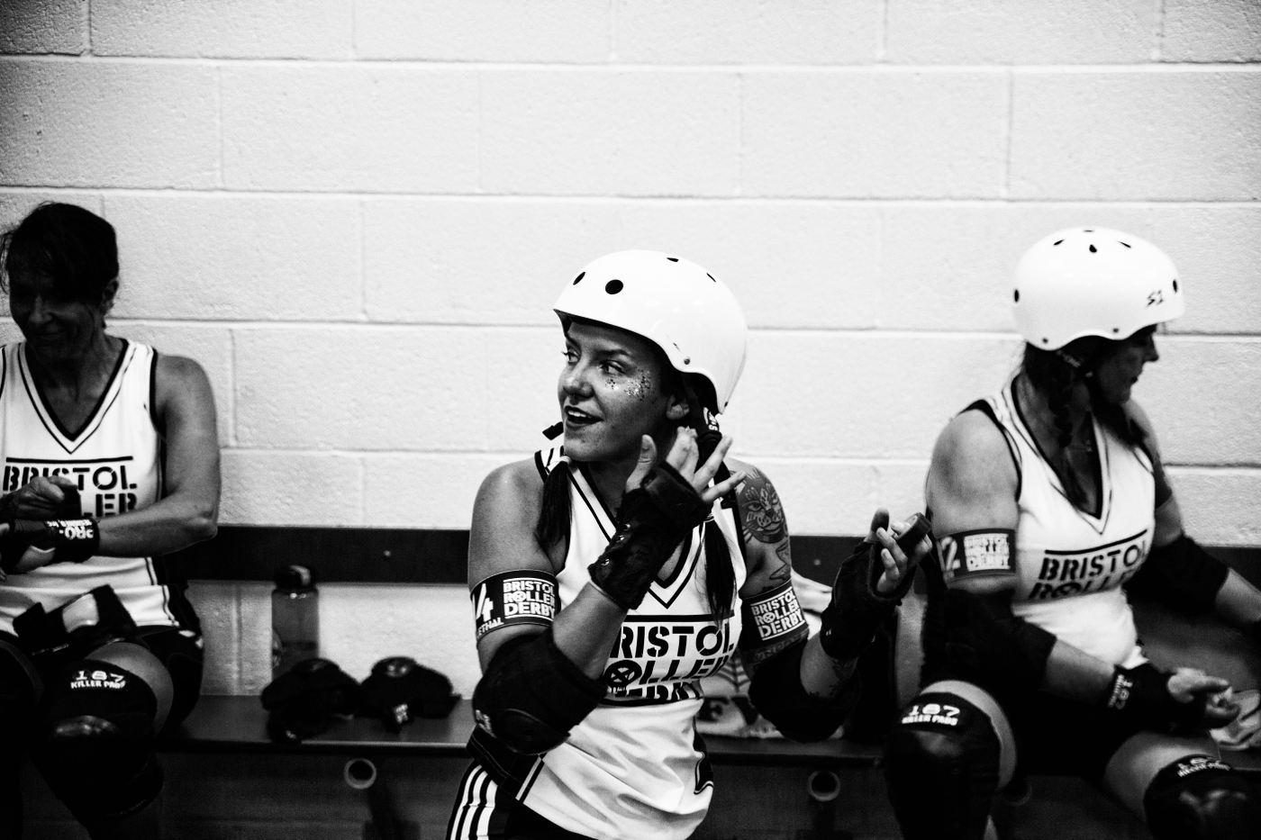 Glittery smiling women buckels up her helmet on the side lines