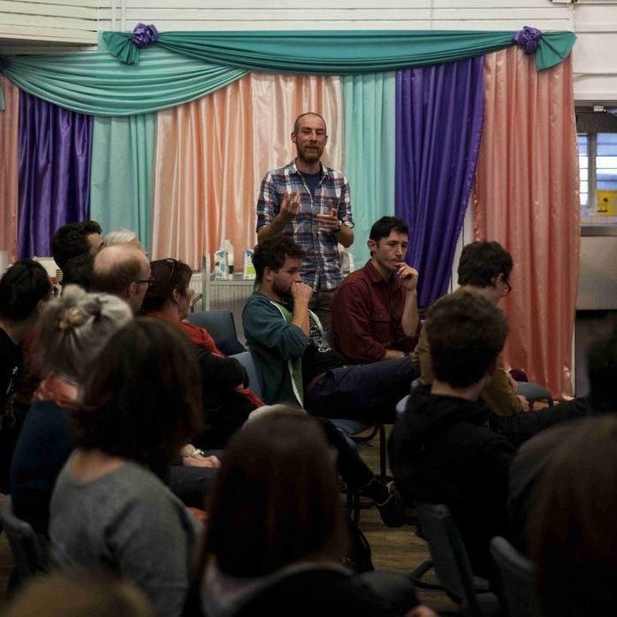 a gentlemen talking to a crowd of enthused folks