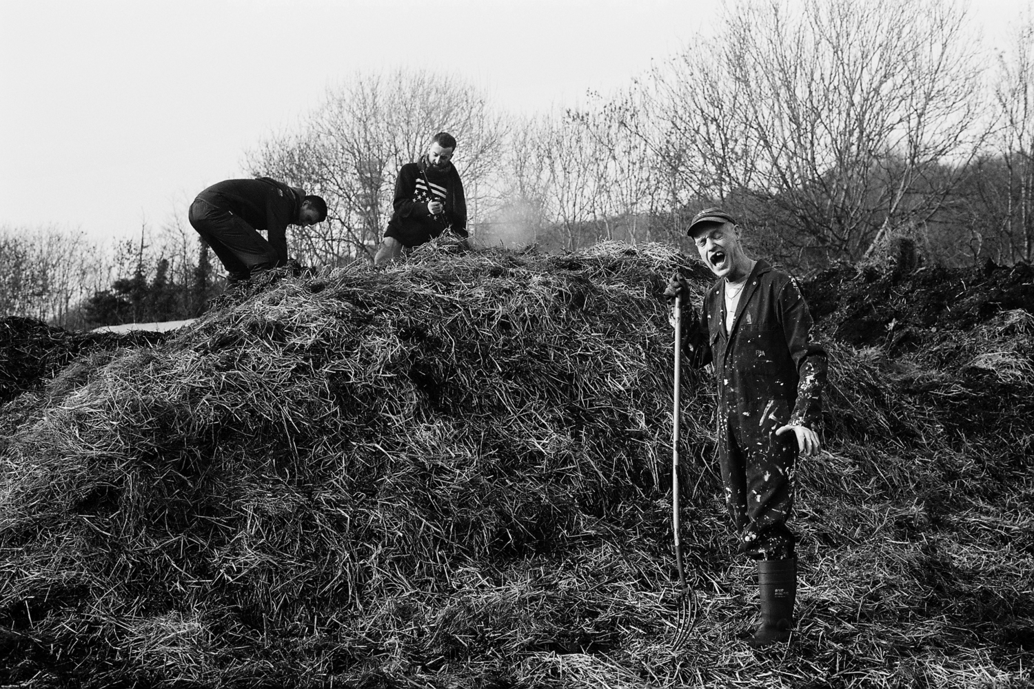 three folks digging over a pile of straw