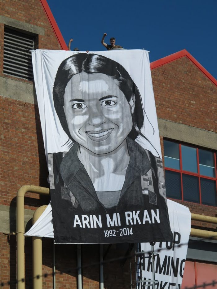 arin mirkan's face painted on a long thin banner in black and white
