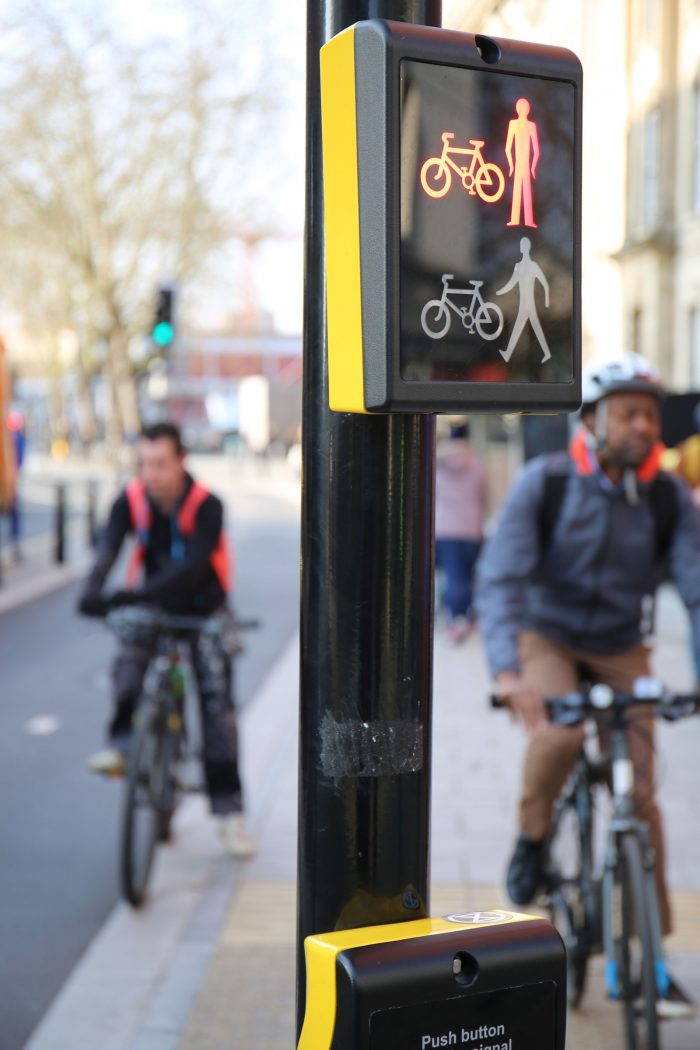a pedestrian/bike crossing button with cyclist in the background